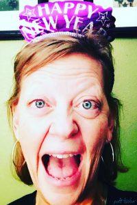 joyful woman's face wearing a happy new year hat
