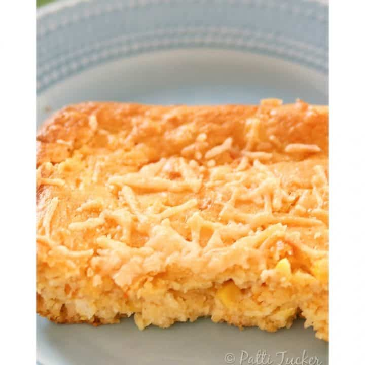 a slice of corn fritter casserole on a blue plate