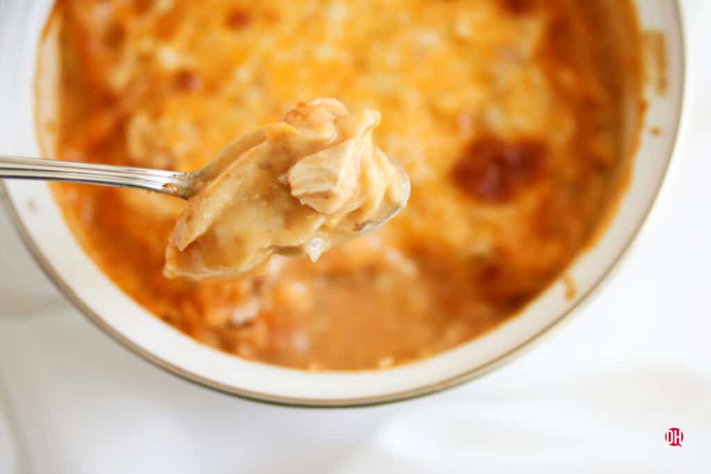 spoon holding bite of king ranch chicken over a baked dish