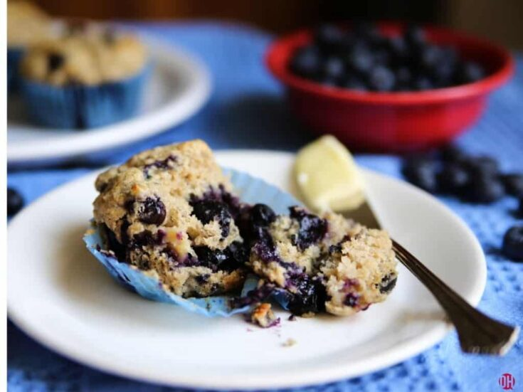 blueberry muffin halfed on white plate with knife with butter on it.